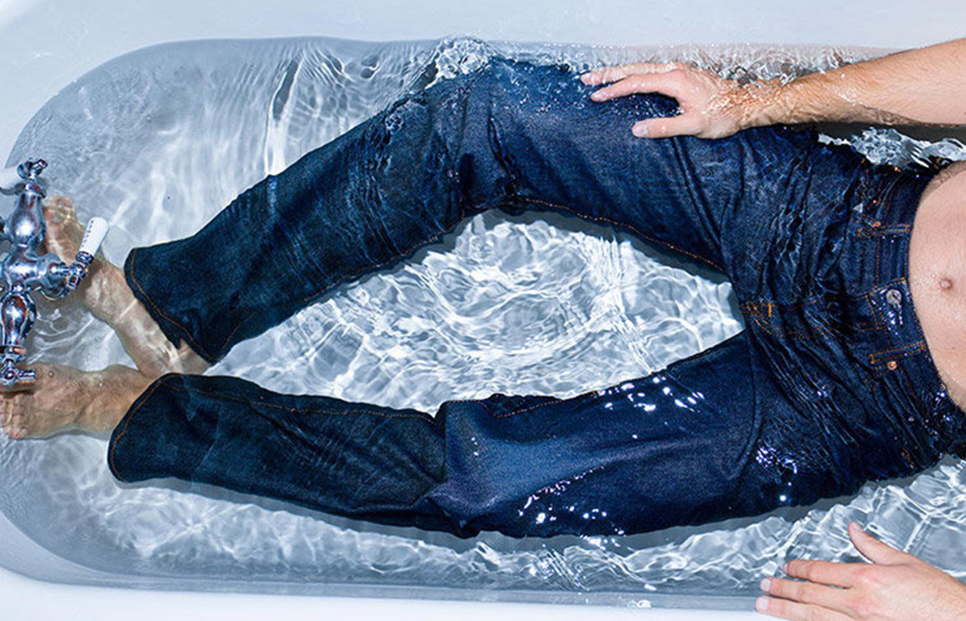 Man lying inside a bathtub full of water wearing a levi's 501 Shrink to fit